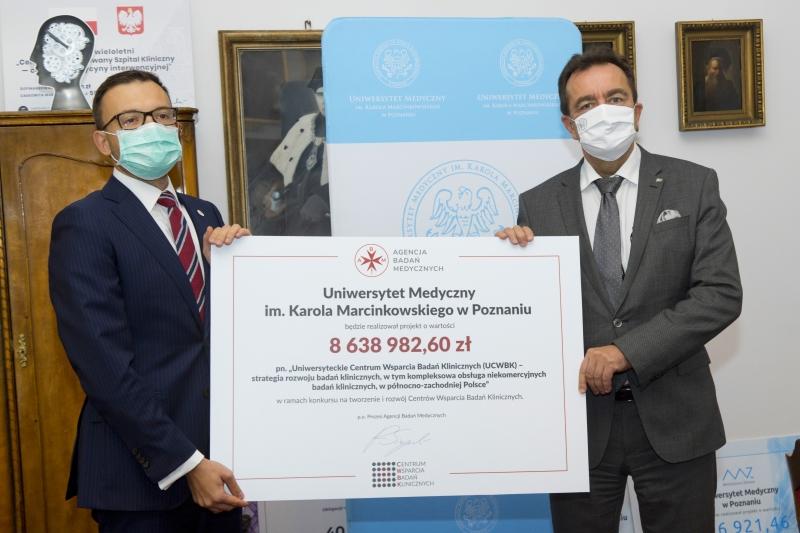 Dr Radosław Sierpiński i prof. Andrzej Tykarski trzymają symboliczny czek
