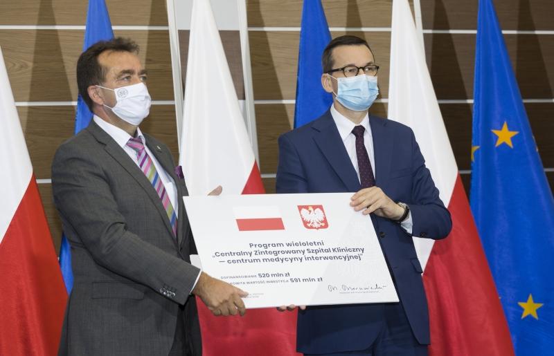 Rektor Andrzej Tykarski i premier Mateusz Morawiecki trzymają symboliczny czek