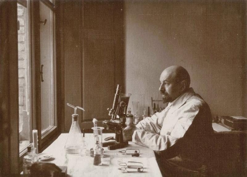 Profesor Adam Wrzosek siedzi przy stole. Patrzy w kierunku okna. Na stole stoi mikroskop.