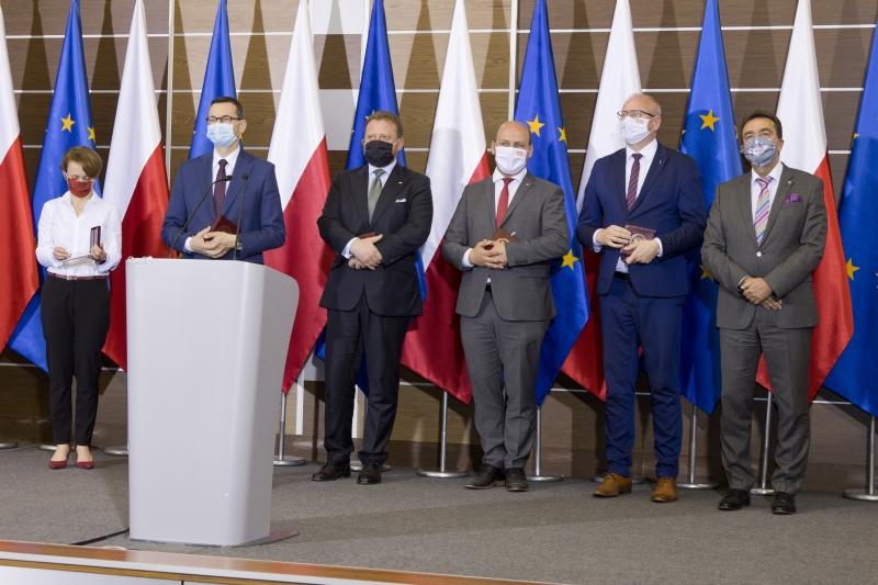 Zaprszeni goście stoją na tele flag Polski i Unii Europejskiej
