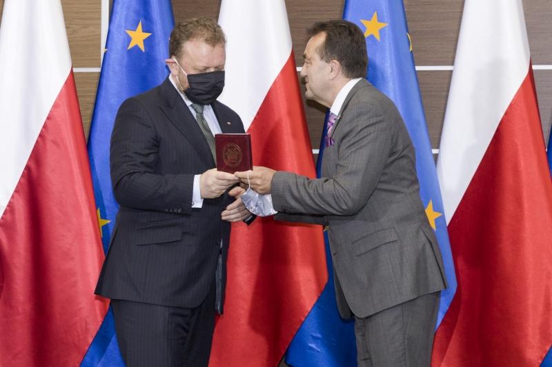 Łukasz Szumowski odbiera Medal od Andrzeja Tykarskiego